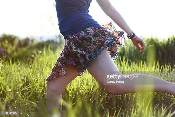 woman running through grass - skirt blowing stock photos and pictures