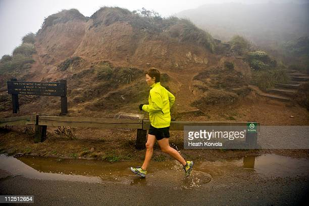 woman running through mud puddle on trail run. - newhealth stock pictures, royalty-free photos & images