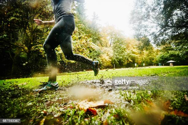 Woman running through mud while on run in park