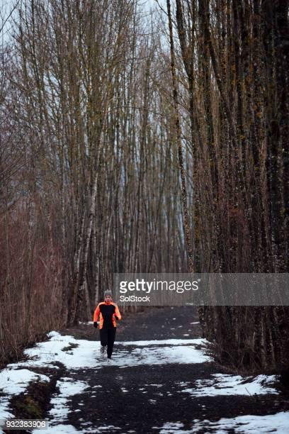 Woman Running Through Snowy Woodland