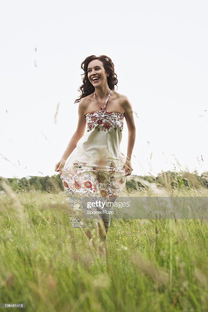 Woman running through wild meadow : Stock Photo