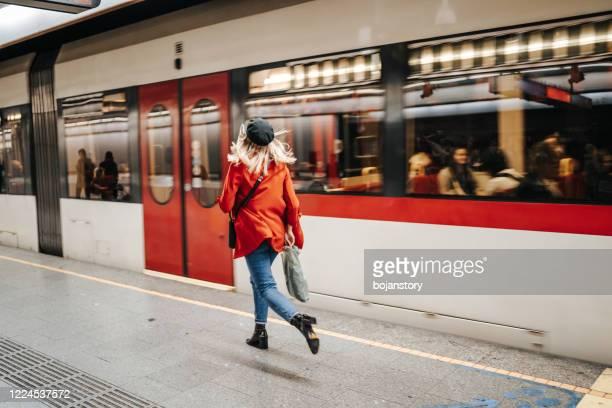 vrouw die de trein loopt - hoofddeksel stockfoto's en -beelden