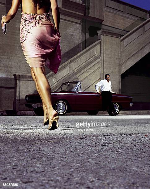 Woman running to man standing next to convertible