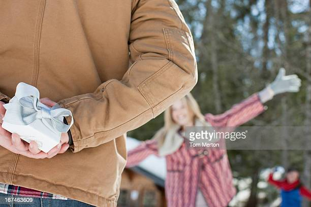 frau läuft in richtung mann hält weihnachtsgeschenk im schnee - nur erwachsene stock-fotos und bilder