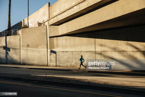woman running under bridge on sidewalk in city - los angeles città foto e immagini stock