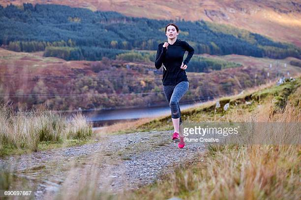 woman running up a hill in the wilderness - jogging stock pictures, royalty-free photos & images