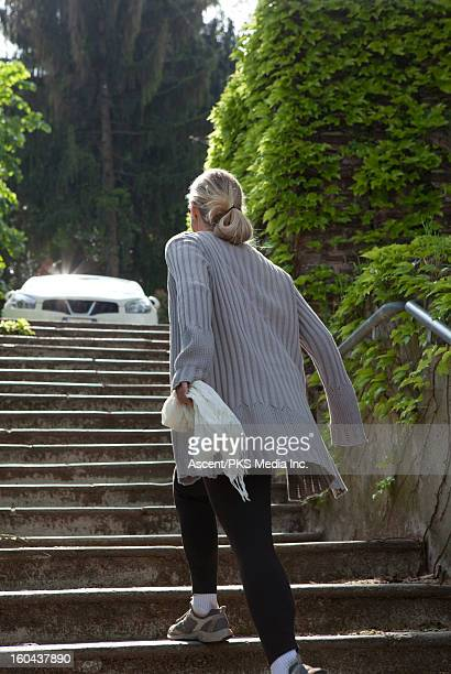 Woman running up a stone staircase towards a car