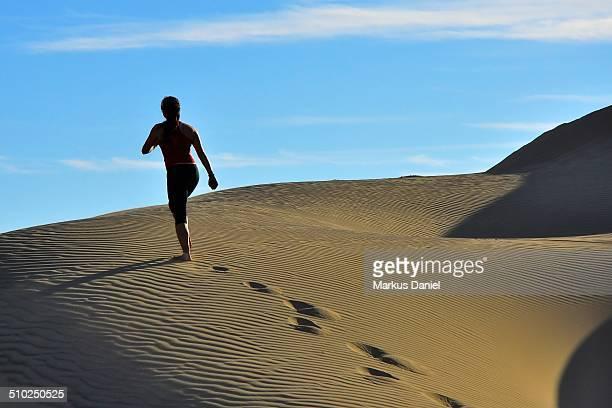 """woman running up sand dunes in huacachina desert - """"markus daniel"""" stockfoto's en -beelden"""