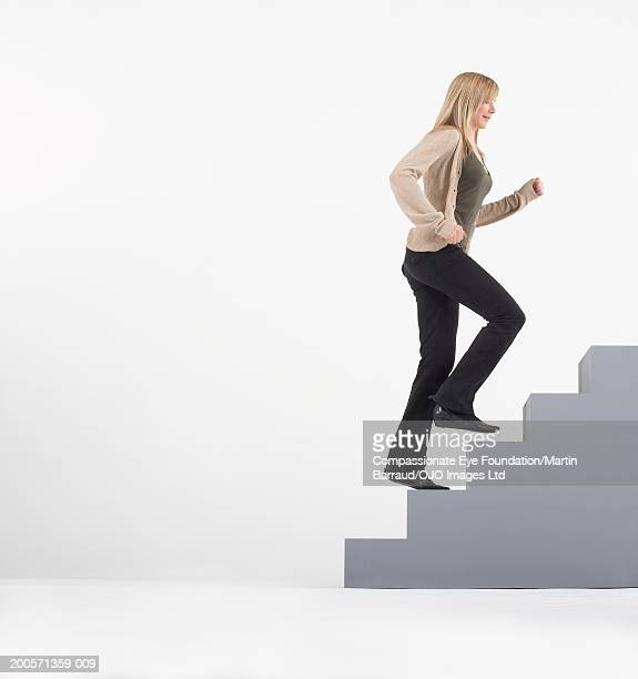 Woman running up stairs, side view