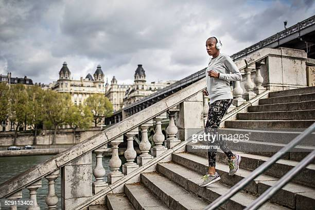 Woman running up steps at Paris