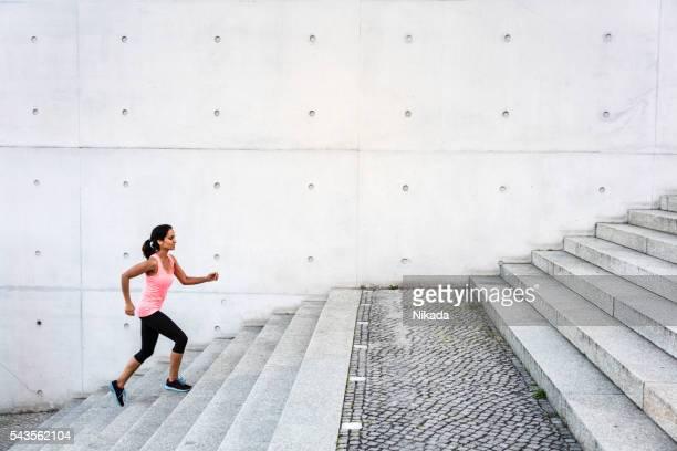 Femme monter les marches dans un cadre urbain