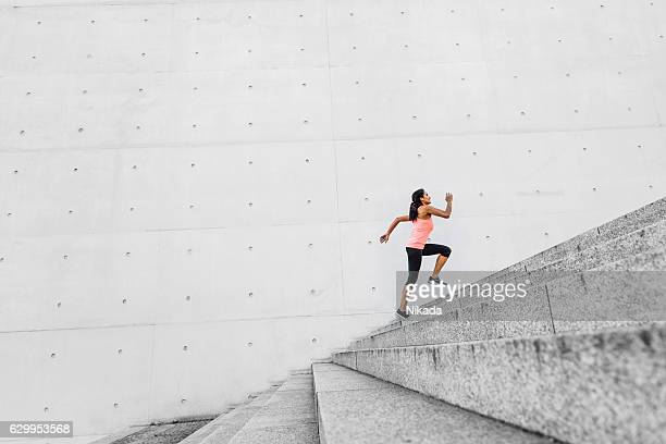 woman running up steps in urban setting - steps stock photos and pictures