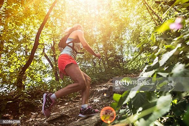 Frau Laufen bergauf auf einer felsigen Pfad