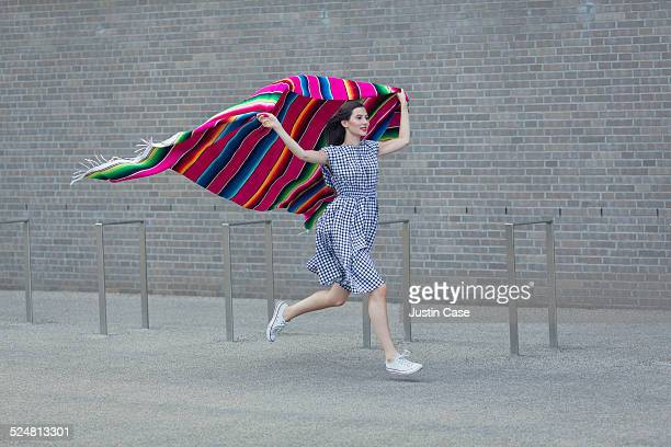 woman running while holding a colorful blanket