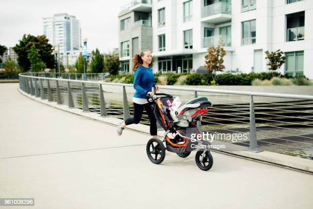 woman running with baby stroller on footpath in city - three wheeled pushchair stock pictures, royalty-free photos & images
