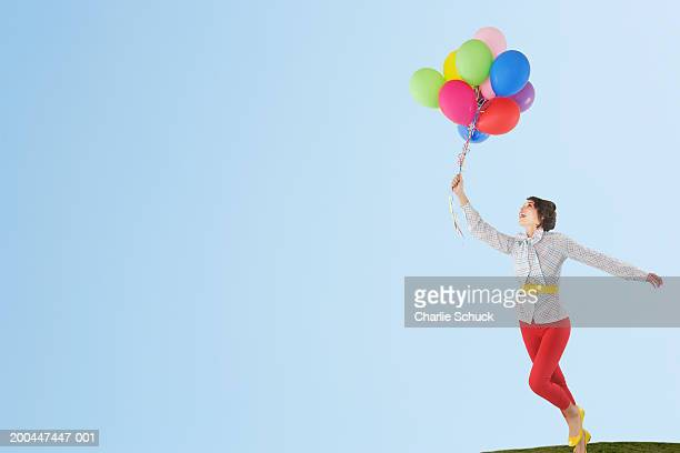 Woman running with balloons, looking up