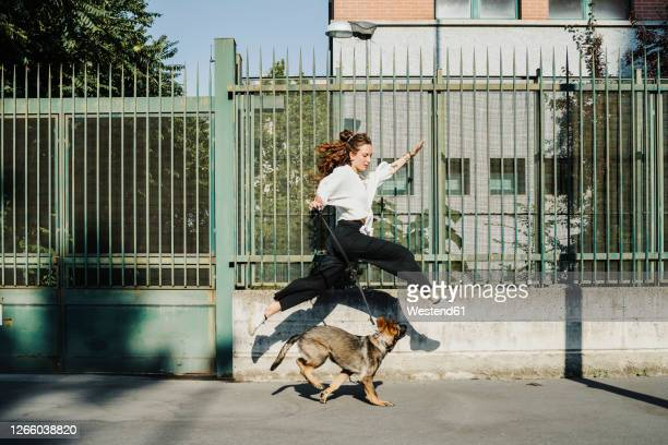 woman running with dog at sidewalk in city - mid adult stock pictures, royalty-free photos & images