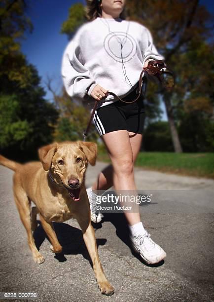 woman running with dog - hairy woman stock-fotos und bilder