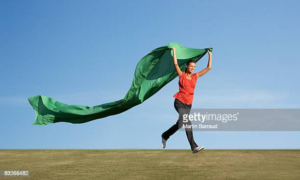 Woman running with green fabric