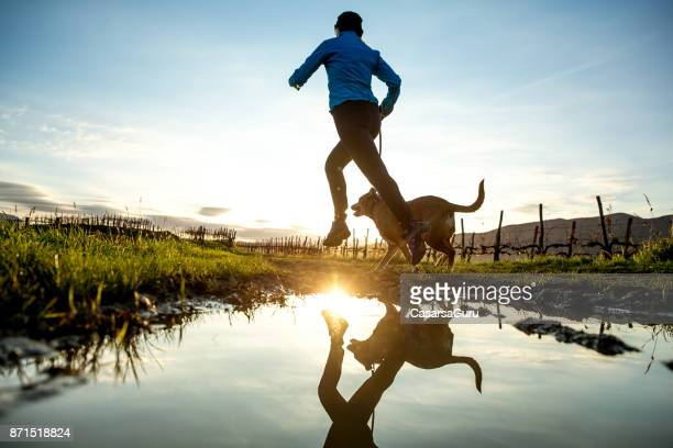 woman running with her dog on muddy dirt road - animal welfare stock pictures, royalty-free photos & images