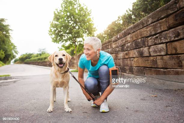 woman running with her dog - termine sportivo foto e immagini stock