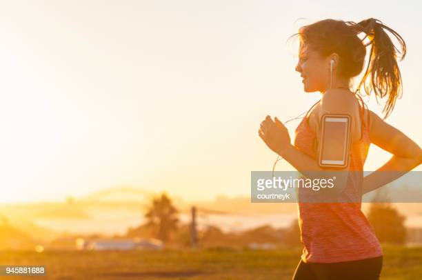 woman running with mobile phone on her arm. - running stock pictures, royalty-free photos & images