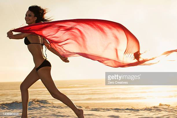 Woman running with sarong on beach