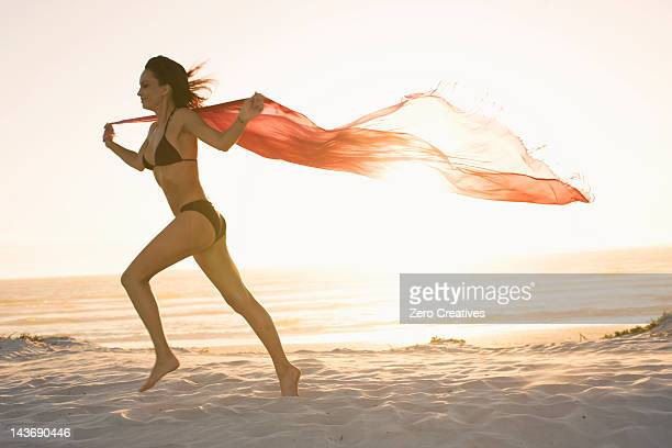 woman running with sarong on beach - sarong stock photos and pictures