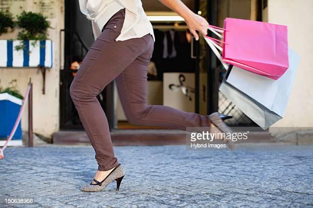 Frau läuft mit Einkaufstaschen
