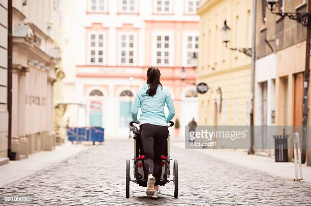 Woman running with stroller in the city