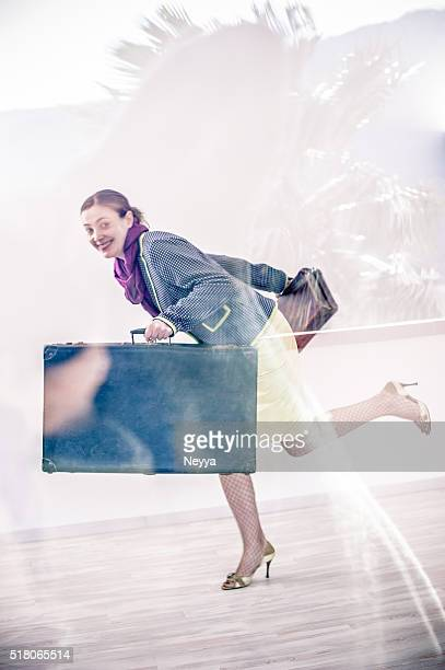 Woman running with suitcases
