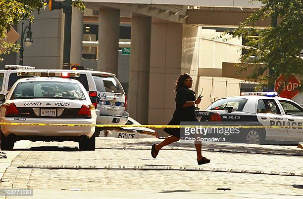 A woman runs across Ellsworth Drive past police cars as a man holds a hostage in the lobby of the Discovery Communications building September 1 2010...