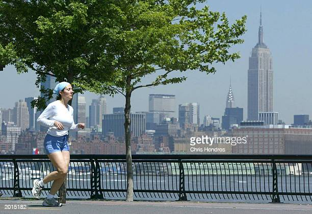 A woman runs along the Hudson river with the Manhattan skyline in the background May 19 2003 in Hoboken New Jersey Temperatures in the 70s and almost...