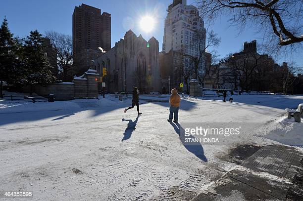 A woman runs and a man walks through Central Park in frigid temperatures January 22 2014 in New York The northeastern US shivered amid heavy snowfall...