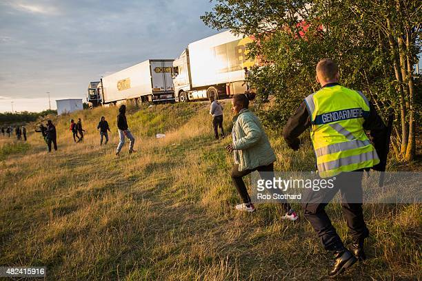 A woman runs away from Gendarmerie near the Eurotunnel terminal in Coquelles on July 30 2015 in Calais France Hundreds of migrants are continuing to...