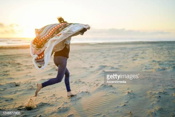 女性は日の出時にビーチを駆け下りる - 30代の女性だけ ストックフォトと画像
