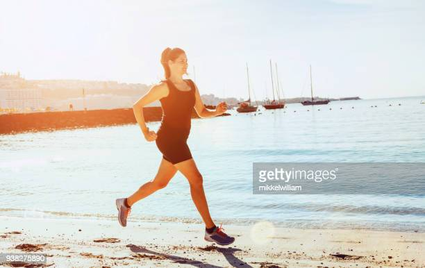 woman runs endurance race on a beach while the sun shines - hot spanish women stock pictures, royalty-free photos & images