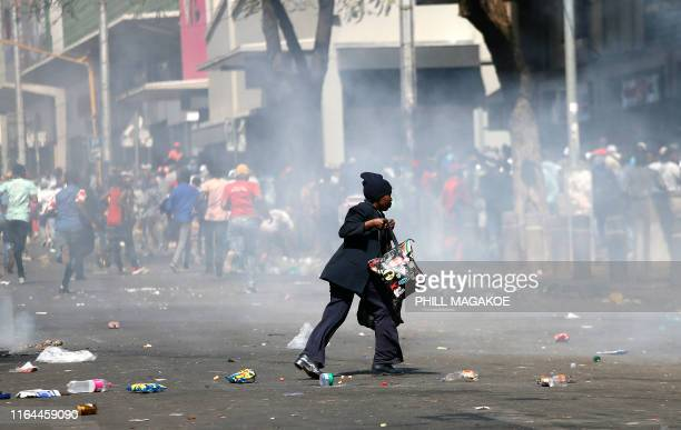 TOPSHOT A woman runs for cover during the rioting of taxi drivers near the Bloed Taxi Rank on August 28 in Pretoria Central Business District South...