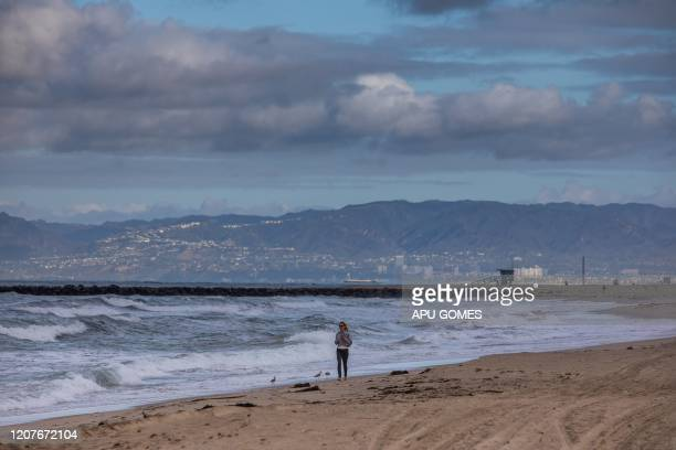 Woman runs in the morning at El Segundo beach in Los Angeles, California on March 19, 2020. - The US government is now preparing for 18 months of the...