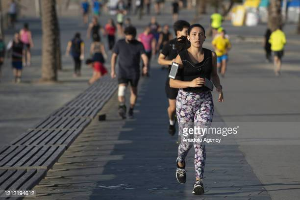 Woman runs on La Barceloneta Beach in Barcelona, Spain on May 8, 2020. The government opened the beaches for the first time since Spain declared a...