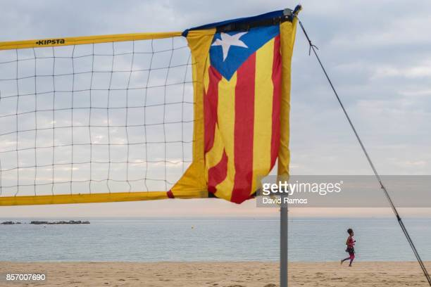 A woman runs past a beach volley ball court with a Catalan Proindependence flag known as 'Estelada' tied to the net at the Barceloneta beach as a...