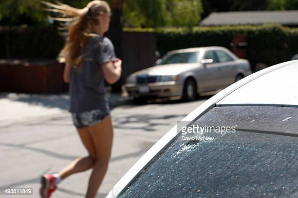 A woman runs past a car with a bullet hole in the window at a crime scene May 25 2014 in Isla Vista California According to reports 22 year old...