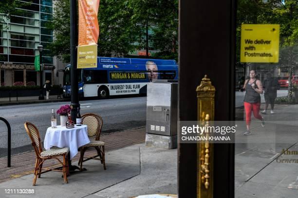 TOPSHOT A woman runs past a set bistro table outside a restaurant amid the novel coronavirus pandemic in Atlanta Georgia on April 27 2020 Some...