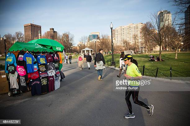 A woman runs past a vendor selling 'Boston Strong' sweatshirts and other apparel in Boston Common on April 12 2014 in Boston Massachusetts Two...