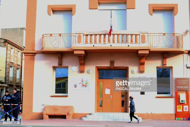 A woman runs past the community center of of SaintFeliud'Avall with a flag at halfmast on December 15 a day after some children from the town were...