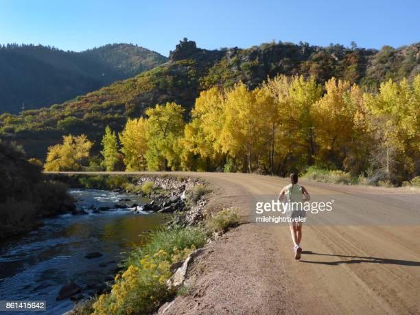 Woman runs South Platte River Waterton Canyon Colorado fall colors Rocky Mountains