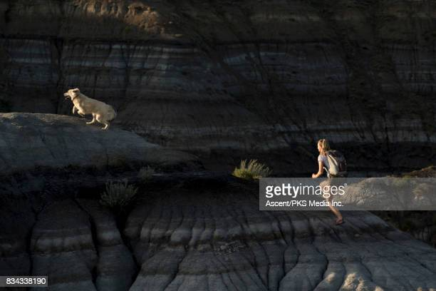Woman runs through badlands with dog