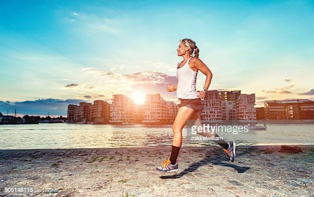 Woman runs  through the city at sunset