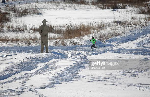 A woman runs through the snow along the Detroit River February 2 2015 in Detroit Michigan Detroit received over a foot of snow during a storm that...