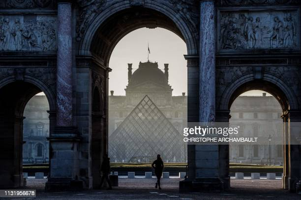 TOPSHOT A woman runs under the Arc de Triomphe du Carrousel by the Louvre museum pyramid in the morning haze at dawn in Paris on March 22 2019...